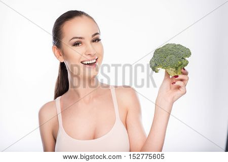 Joyful young woman is showing broccoli and smiling. Isolated