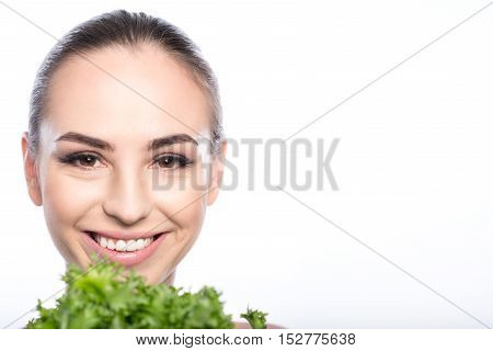 Happy young woman is holding lettuce near her face and smiling. She is looking at camera with aspiration. Isolated and copy space in right side