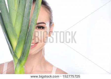 I prefer healthy diet. Happy girl is covering half of her face by leek. She is standing and smiling. Isolated and copy space in right side