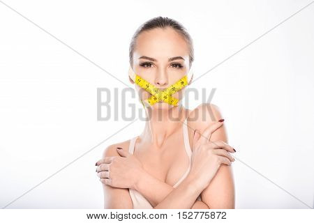 You must stick to a diet. Hungry young woman is standing with her mouth covered by tape. She is looking at camera with seriousness. Isolated and copy space in left side