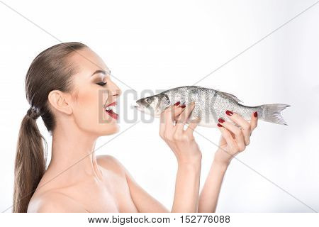 Healthy girl is holding fish and laughing. She is standing with naked shoulders. Isolated