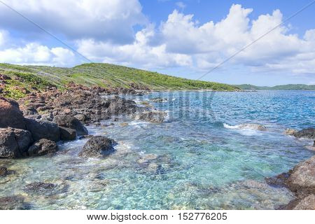 Small waves of clear turquoise water roll against rocky beach of Soldier's Point on Caribbean island paradise of Isla Culebra in Puerto Rico