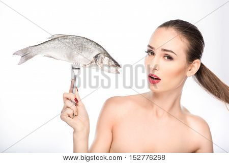Sympathetic young woman is holding fish on fork. She is standing and looking at camera with pity. Isolated