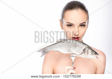Healthy young woman is holding raw fish on fork. She is standing and looking at camera with desire. Isolated and copy space in left side