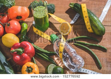 Close up of vegetables and fruits near bottle of water and juice wrapped by tape on table