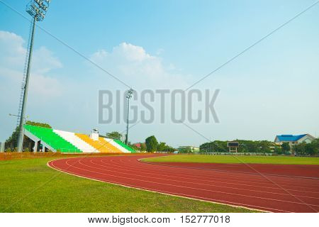 Red treadmill Red running track at the stadium with green grass on blue sky