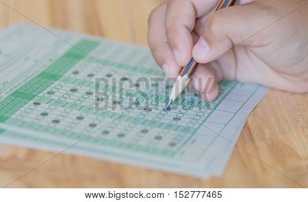 student testing in exercise exams answer sheets on table