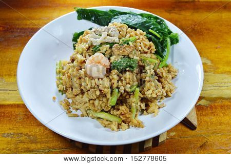 fried egg rice with pork and Chinese kale in black soy sauce topping shrimp on dish