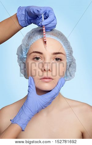 Attractive young woman gets cosmetic injection an injection in the upper lip over blue background. Doctors hands making an injection in face close-up. Beauty Treatment. shot in the forehead