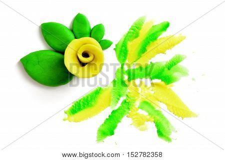 Yellow rose with green leaves made of plasticine on a white background. Flowers of modeling clay. Handmade art. Creative work.