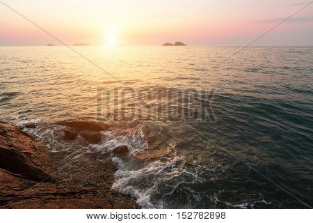 Surf on the rocky seashore during sunset.