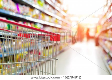 Supermarket aisle on both sides of the shelves and red trolleys.