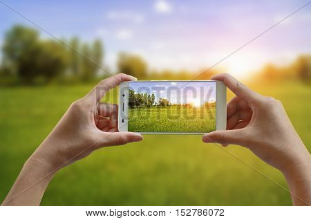 hand taking photo of beautiful nature and sunrise with cell mobile phone concept