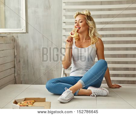 Young attractive woman eating a piece of delicious pizza. She a T-shirt jeans and sneakers sitting on the floor at home. Food delivery.