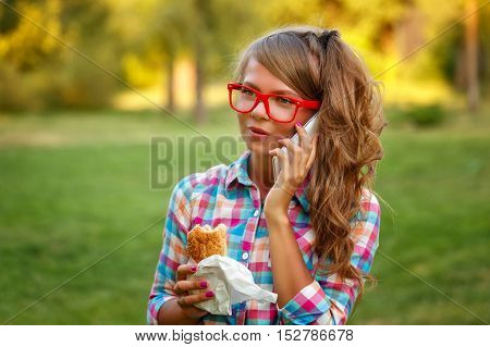 Pretty attractive girl talking on the phone and holding a hot dog in a park. Snack. Fast food.