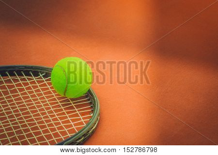 Tennis Ball with Racket on the clay tennis court. vintage