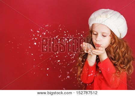 Little girl in white hat blowing snow with her hand.