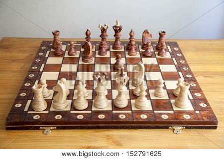 chess pieces on the chessboard on the wooden table.