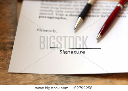 Pens and paper are placed in the working document for a signature.