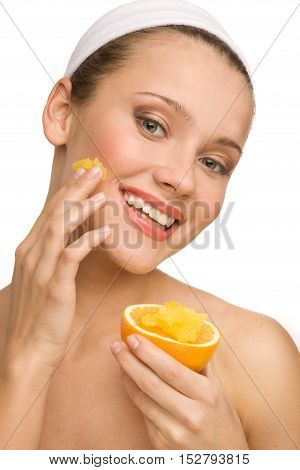 Young cheerful girl with orange in her hand applying natural orange scrab