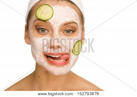 Beautiful woman with the mask on her face is trying to reach cucumber with her tongue