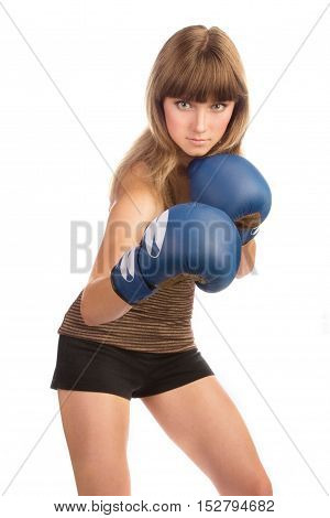 Active young woman stands with lifted blue boxing gloves on her hands