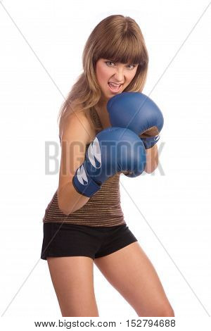 Active young female stands with lifted blue boxing gloves on her hands and screams