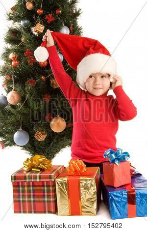 Little boy with presents is sitting by the christmas tree; isolated on white background