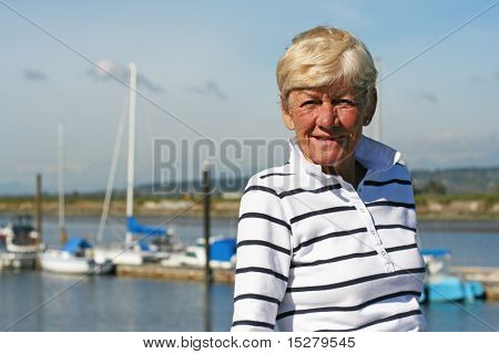 Sixty five year old lady, outside, sailboats in the background.