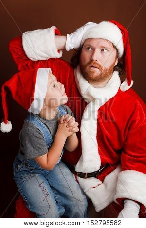 Mandressed in Santa costume looks tired and unhappy Boy is sitting on Santas knee and sharing his Christmas wishes