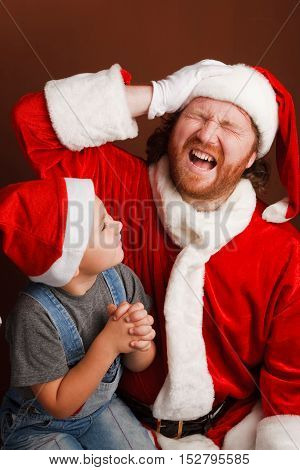 Boy is sitting on Santas knee and sharing his Christmas wishes Mandressed in Santa costume looks exhausted and screams