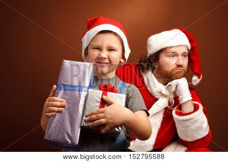 Cheerful and sly boy goes away with presents leavivg behind exhausted Santa Claus