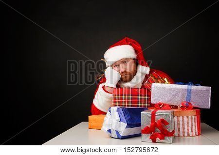 Thoughtful man in santa costume is sitting alone with heap of presents