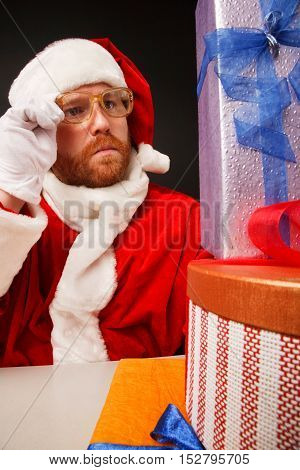 Thoughtful man in santa costume is checking presents