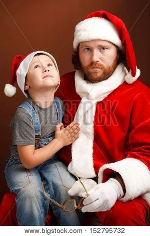 Boy is sitting on Santas knee and asking about his future present. Mandressed in Santa costume looks tired and unhappy