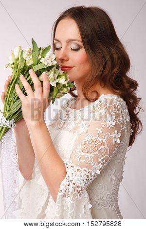 Bride dressed hippie style enjoying her bouquet