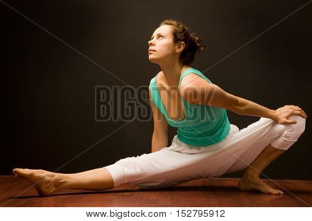 Young yoga instructor woman  doing yoga indoors