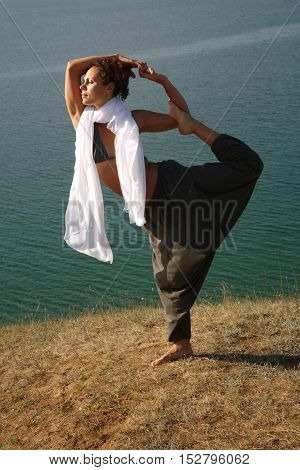 Real yoga instructor practicing near the lake.