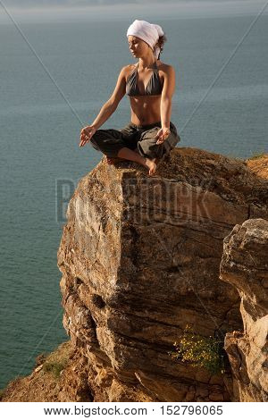 Woman meditating on the rock near water line
