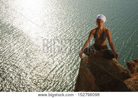 Woman meditating on the rock near water.Copyspace