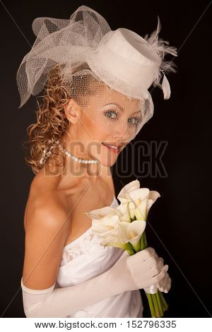 Portrait of a bridedressed in retro style with bouquet made of calla Lily on the black background