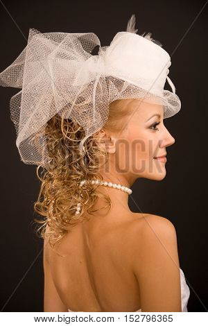 Profile of the stunning bride dressed in retro style hat on the black background