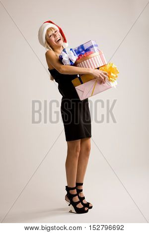 Cheerful young woman win Santa hat is standing on one leg with heap of gifts