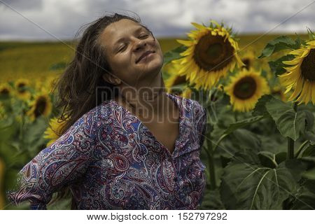 Joyful young girl relaxed in sunflowers field