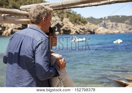 Middle aged couple relaxing on a jetty by the sea, Ibiza
