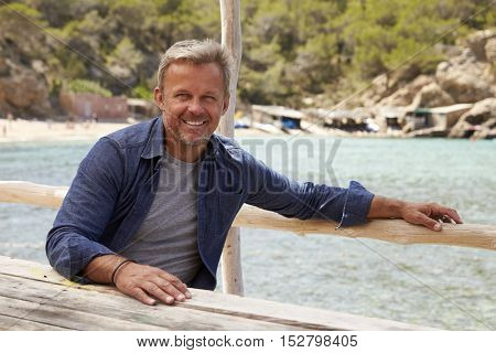 Middle aged Caucasian man sitting at a table by the sea