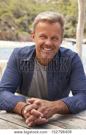 Middle aged Caucasian man sitting at a table on a jetty