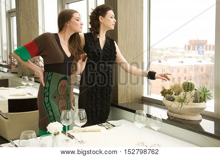 Two young woman are standing in the fancy restaurant and looking through the window.Selective focus with a plant at the foreground