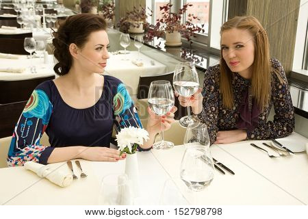 Two young woman are drinking while waiting their order in the restauran
