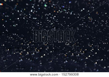 Water drops with rainbow glitter on a dark background. Abstract background.